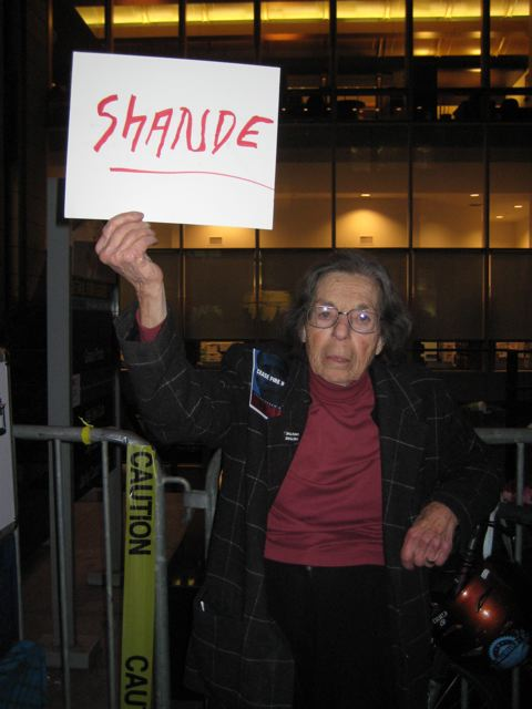 Jean Pauline, San Francisco feminist anarchist activist, died on November 23, 2016. She is holding a sign at a Women in Black demonstration that says Shande, the Yiddish word for shame.