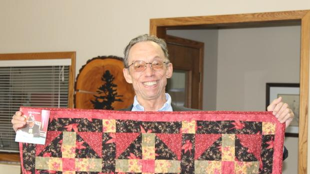 photo of John Iverson with quilt